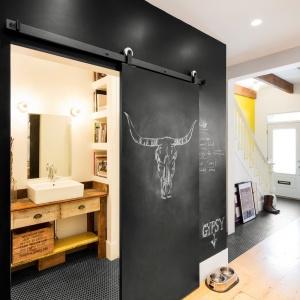 Do łazienki na parterze prowadzą przesuwne drzwi, pomalowane w całości farbą tablicową. Projekt: MARK+VIVI. Fot. Adrien Williams.