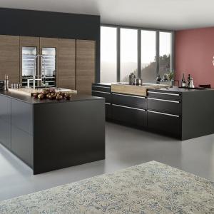 Piękna kuchnia z dwiema wyspami, które są niemal w całości grafitowe i matowe. Wyjątek stanowią okolice powierzchni roboczych, wykończone jasnym drewnem, efektownie kontrastującycm z ciemnymi powierzchniami. Z kolei wysoka zabudowa wkomponowana w ścianę zdobi poziomy rysunek drewna. Fot. Leicht, kuchnia Bondi.