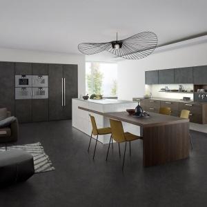 Drewniany stół połączony z wyspą oraz harmonizująca z nim podwieszana dolna zabudowa to elementy ocieplające wystrój tej kuchni, w której prym wiodą fronty pokryte prawdziwym betonem. Fot. Leicht, kuchnia TOPOS   Concrete.