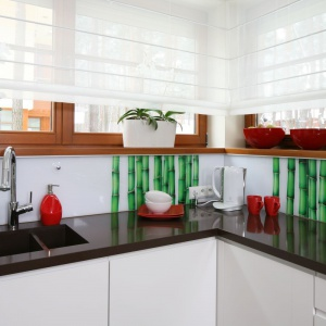 Fototapeta z soczyście zielonymi bambusami ożywia przestrzeń tej kuchni, tworząc piękny zestaw z czerwonymi akcesoriami. Projekt: Katarzyna Mikulska-Sękalska. Fot. Bartosz Jarosz.