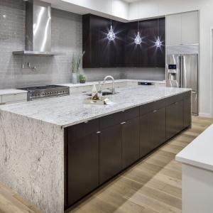 Kuchnia z dużą wyspą zachwyca pięknym marmurowym blatem oraz połyskującymi płytkami jak kafle na ścianie. Projekt: Clark | Richardson Architects. Fot. Paul Finkel.