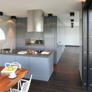 Kuchnia w stylu loft w przeważającej mierze jest szara. Szare, delikatnie wpadające w błękit są meble kuchenne oraz ściana wykończona betonem architektonicznym. Projekt: Justyna Smolec. Fot. Bartosz Jarosz.