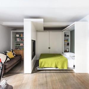 We wnętrzu jedna ze ścian jest mobilna i porusza się po osi w poprzek wnętrza. W nocy odsłania chowane w szafie łóżko i oddziela sypialnię od salonu, w dzień - scala się ze ścianą. TV zamocowany w ścianie obraca się o 180 stopni i pozwala na wygodne oglądanie zarówno z salonu jak i sypialni. Projekt: Michael Chen, Braden Caldwell/MKCA Michael K Chen Architecture. Fot. Alan Tansey.