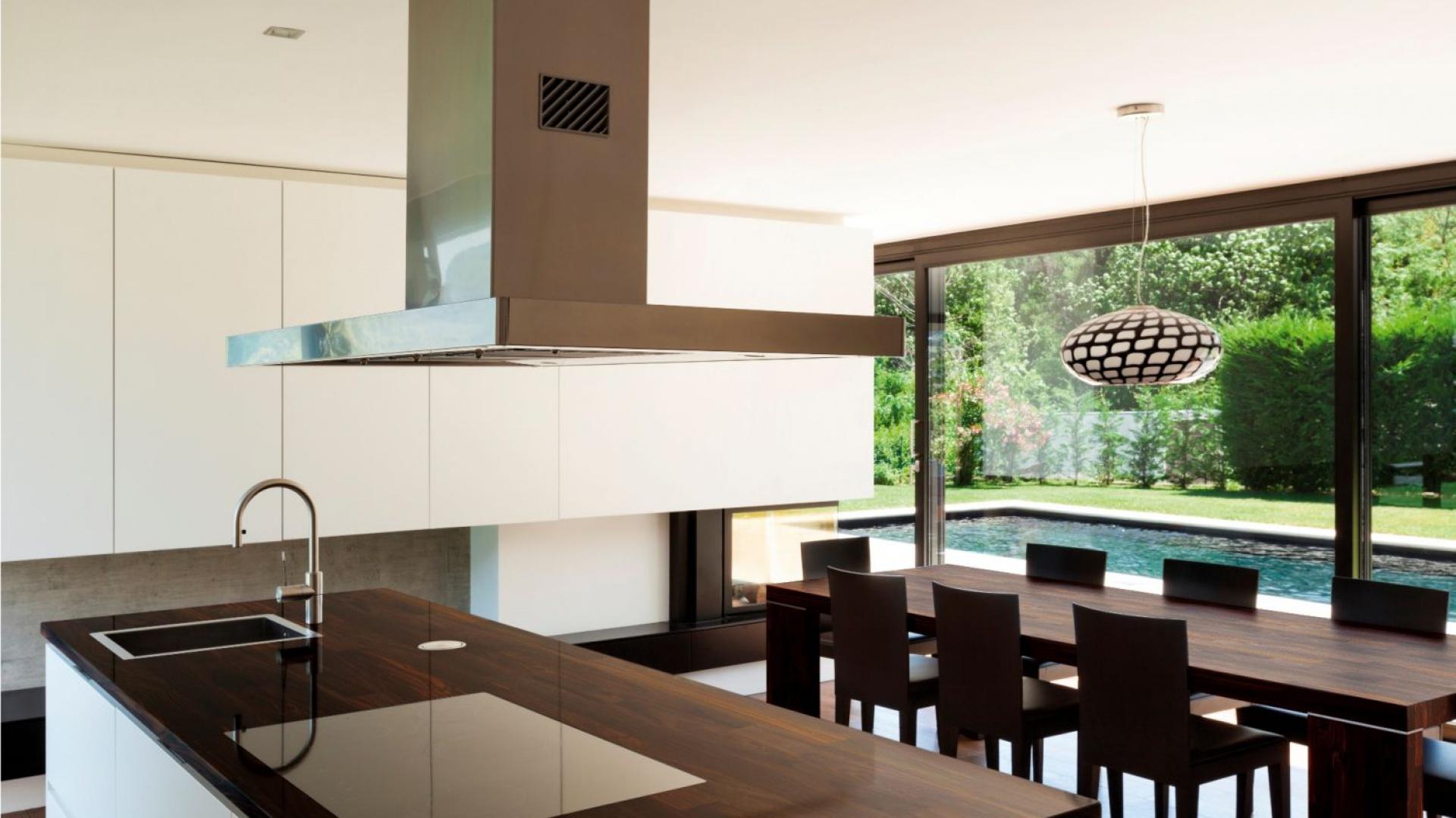 Naturalne drewno palisandrowe jest surowcem z jakiego wykonano blat w tej nowoczesnej kuchni. Pięknie wieńczy jasną wyspę kuchenną. Fot. DLH.