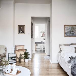 Plecione krzesło, drewniana podłoga i stare obrazy oprawione w ramy w miedzianym kolorze czy haftowana poduszka. Wszystkie te elementy nie tylko ocieplają wizualnie wnętrze, ale też nadają mu delikatnie starodawny klimat. Fot. Janne Olander/Stadshem.se.