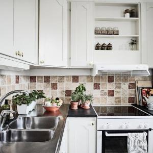 Wśród białych, frezowanych mebli kuchennych schowano nowoczesny sprzęt AGD. Fot. Janne Olander/Stadshem.se.
