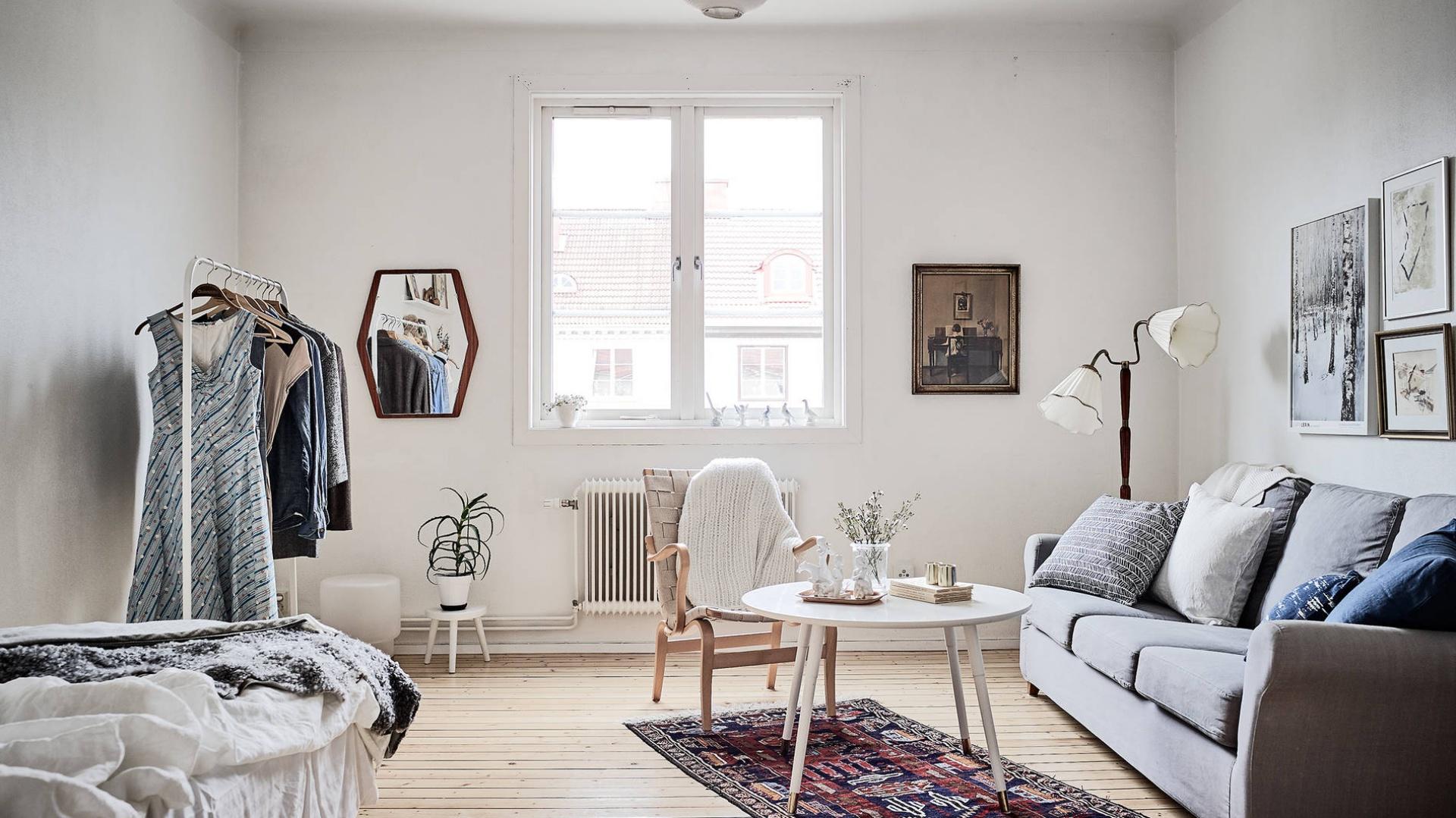 W przestrzeni salonu z sypialnią wzrok przyciąga piękna, stylizowana lampa ze zdobnymi kloszami. Fot. Janne Olander/Stadshem.se.