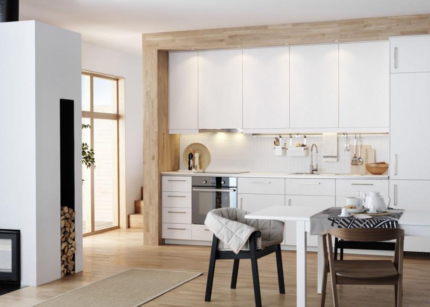 Białe meble kuchenne są wpasowane w ciekawą wizualnie drewnianą ramę, okalającą zabudowę kuchenną. Fot. IKEA.