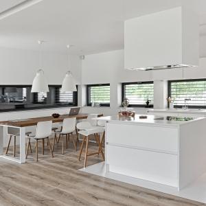 Nowoczesna biała kuchnia, którą ociepliła drewniana podłoga oraz drewniane nogi stołków przy barze kuchennym i drewniany blat stołu w jadalni. Fot. Atlas.