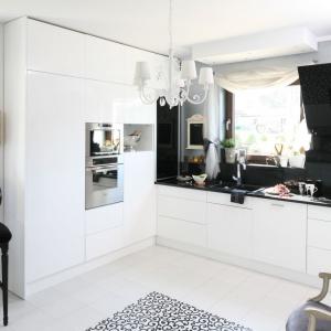 Biało-czarna kuchnia nawiązuje do stylistyki glamour za sprawą połyskującej powierzchni blatu i ściany nad blatem, a także dekoracyjnego, stylizowanego żyrandola. Projekt: Magdalena Konochowicz. Fot. Bartosz Jarosz.