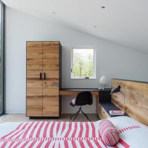 Sypialnia jest jednocześnie przestrzenią do pracy. Biurko połączone z szafą przechodzi w zabudowę, która stanowi praktyczną półkę oraz wezgłowie łóżka. Projekt: Sharon Davis Design. Fot. Elizabeth Felicella