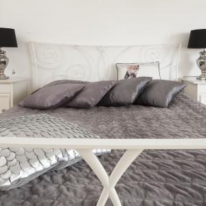 Łóżko zamknięto w zdobne metalowe ramy pomalowane na biało. Projekt: Właściciele. Fot. Bartosz Jarosz.