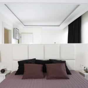 Lustro nad łóżkiem jako dekoracja ściany. Biały zagłówek i złote lampki nocne sprawiają, że wnętrze prezentuje się bardzo elegancko. Projekt: Katarzyna Uszok. Fot. Bartosz Jarosz.