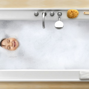 Całą wannę otacza półka z podwyższoną krawędzią, zapobiegającą zsuwaniu się kosmetyków – wanna Bath Gallery z konglomeratu z powierzchnią z akrylowego żelkotu firmy Ravak. Fot. Ravak.