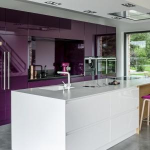 Śliwkowy kolor wysokiej zabudowy wykończonej na wysoki połysk zestawiono z białą, corianową wyspą. Fot. Zajc Kuchnie, kuchnia Z1.