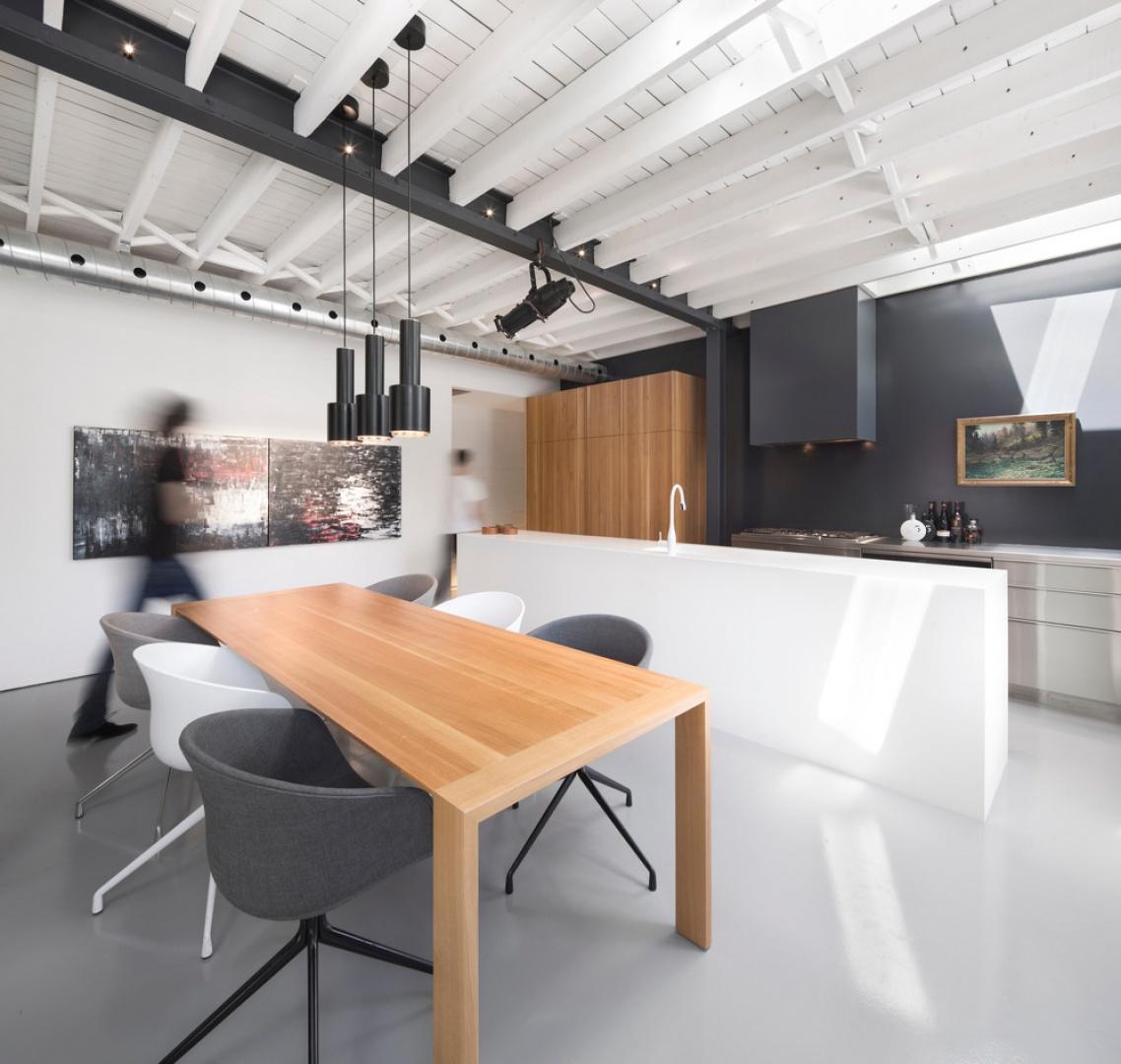 Loftową atmosferę we wnętrzu budują odsłonięte belki stropowe oraz towarzyszące im oświetlenie - zwłaszcza podsufitowa, techniczna lampa. Projekt: Atelier Moderno. Fot. Stéphane Groleau.