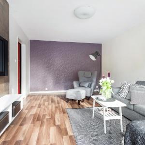Ścianę równoległą do balkonu wykończono tapetą w śliwkowym kolorze. Fot. Svenksfast.se.