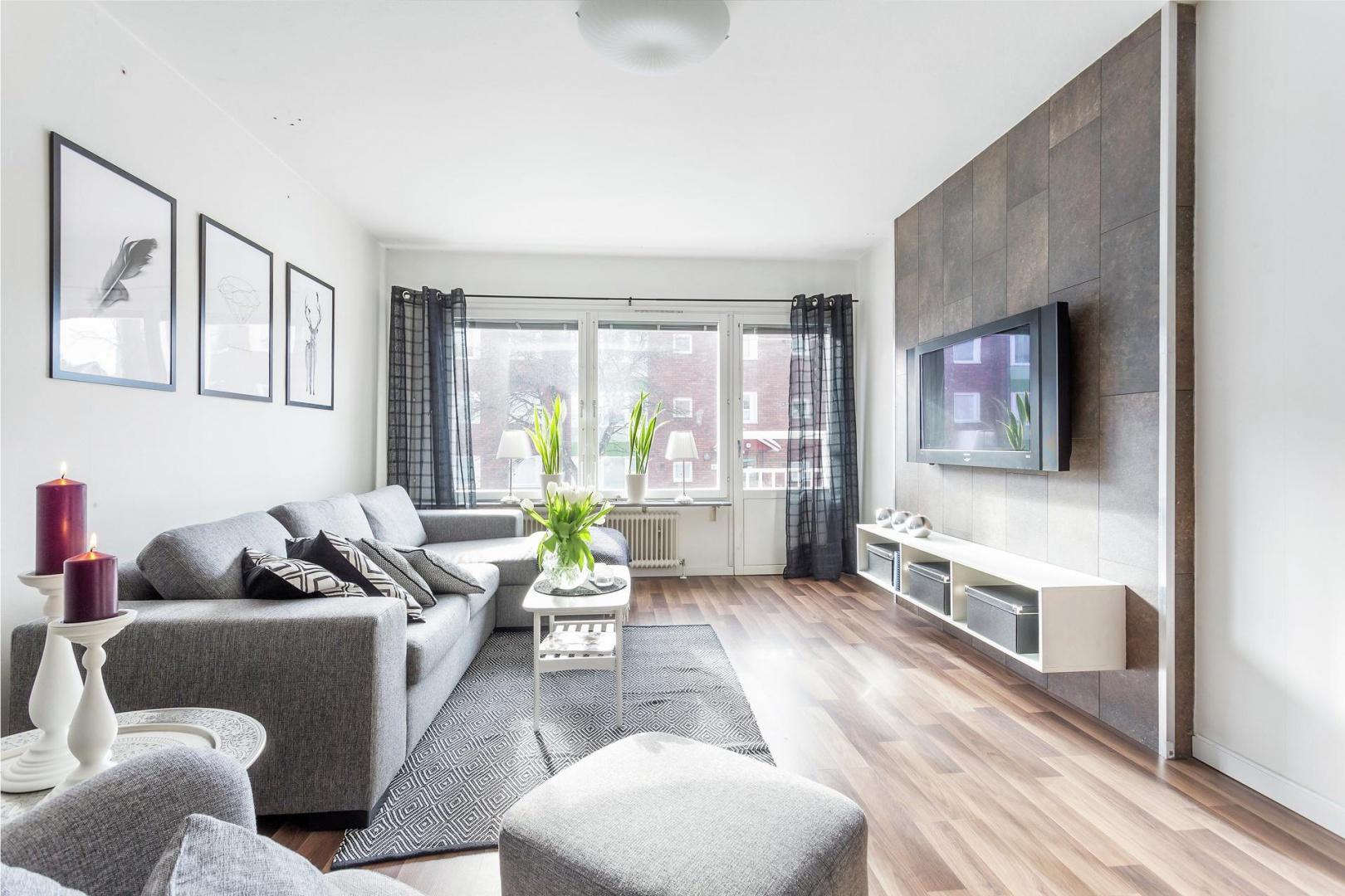Szary salon ujmuje spokojem aranżacji. Stonowane barwy zachęcają do wypoczynku na miękkiej kanapie lub przytulnym fotelu z podnóżkiem. Fot. Svenksfast.se.