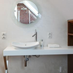 W łazience na piętrze, pod skosem dachowym, jest dużo bieli i drewna. Fot. Bartosz Jarosz.