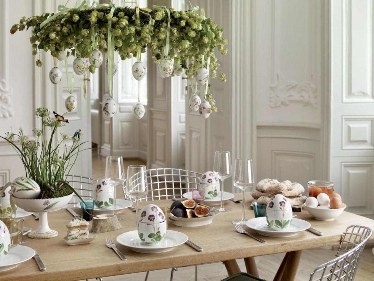 Tutaj dekoracją stołu są porcelanowe jaja pomalowane kolorowymi farbami oraz dekoracyjne zawieszki na dekoracyjnym wianku wiszącym nad stołem. Fot. Royal Copenhagen.