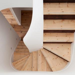Stopnie schodów w krętej klatce schodowej wykończono jasnym odcieniem drewna. Projekt: Scenario Architecture. Fot. Matt Clayton.