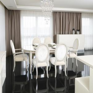 Biały stół i stylizowane tapicerowane krzesła odznaczają się estetycznie na tle połyskującej ciemnej podłogi. Projekt: Katarzyna Uszok. Fot. Bartosz Jarosz.