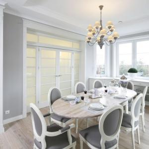 Stół z jasnym, drewnianym blatem zestawiono z stylizowanymi szaro-białymi krzesłami. Projekt: Maciejka Peszyńska-Drews. Fot. Bartosz Jarosz.