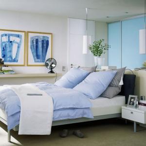 Duża sypialnia z ciekawie zagospodarowaną garderobą, która została usytuowana za wezgłowiem łóżka. Połączenie błękitu i bieli tworzy tu chłodną, ale przyjemną aranżację. Fot. Raumpuls.