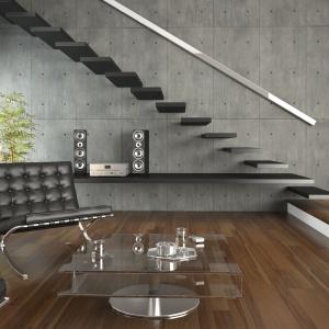 Prostokątne płyty betonowe ułożone w pionie, ozdobione licznymi przetarciami wspaniale komponują się z drewnianą podłogą i skórzanymi meblami wypoczynkowymi. Fot. DekoConcrete.
