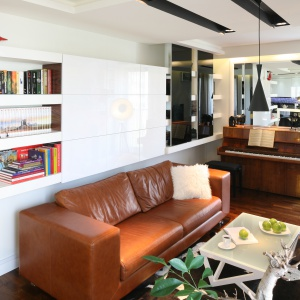 W niewielkim salonie optymalnie wykotrzystano przestrzeń do przechowywania dzięki zabudowie ściennej. Jasne błyszczące wykończenie odbija światło i powiększa przestrzeń. Projekt: Małgorzata Mazur. Fot. Bartosz Jarosz