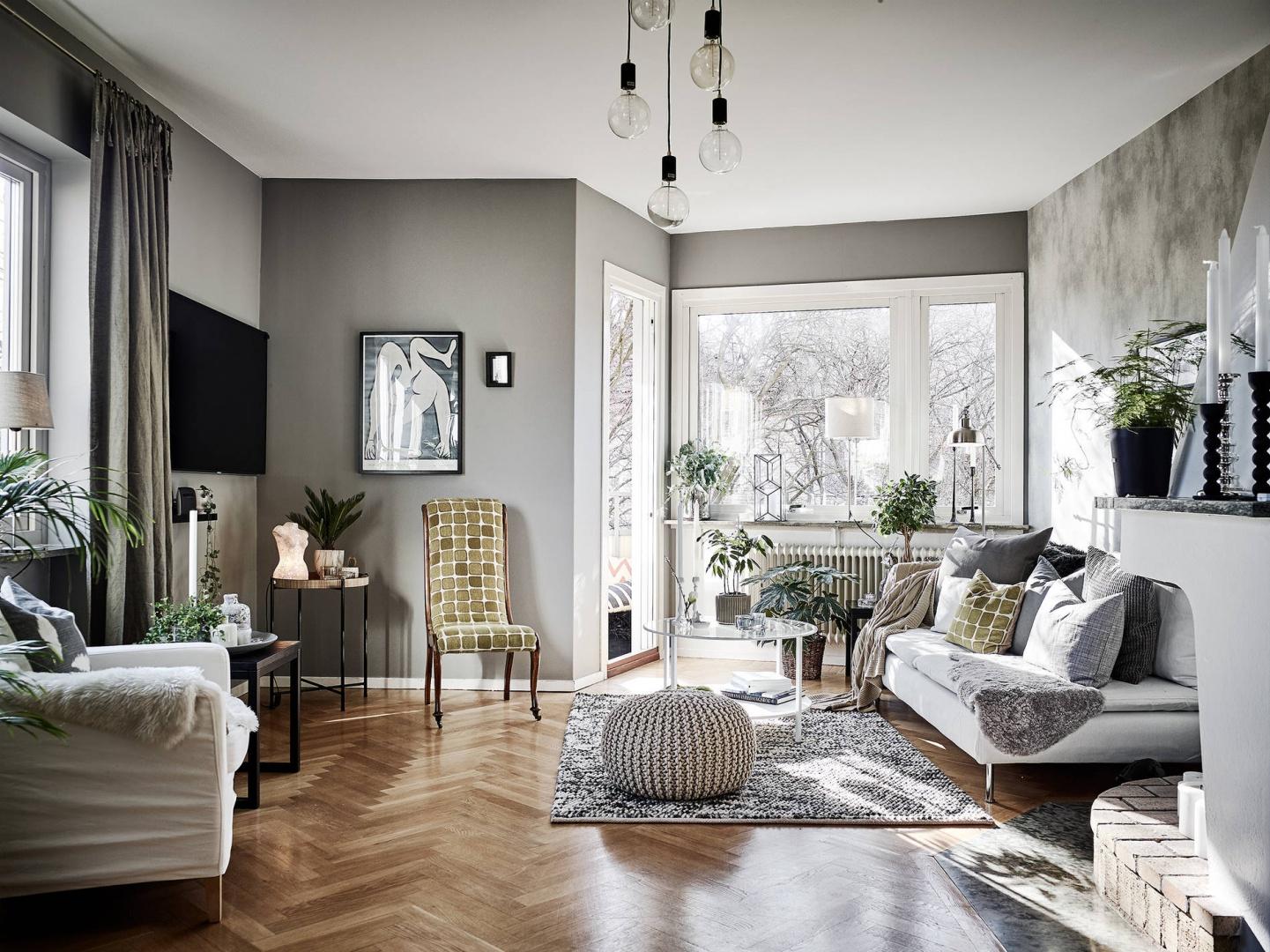 Salon zdominowały szarości. Szare są tutaj ściany, dywan, a nawet meble. Industrialny sznyt wprowadzają żarówki na odsłoniętych oplotach. Fot. Janne Olander/Stadshem.se.