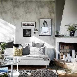 Z lampami w industrialnym stylu ciekawie kontrastuje rustykalny kominek. Fot. Janne Olander/Stadshem.se.