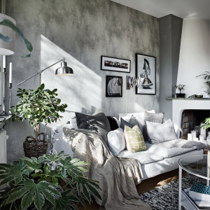 Ścianę za wypoczynkiem wykończono szarym tynkiem z betonowym efektem przetarcia. Fot. Janne Olander/Stadshem.se.