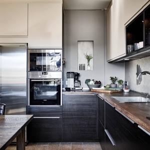 Zabudowa kuchenna jest nowoczesna i dwukolorowa. Fronty górnych szafek mają kolor magnolii, a dolne - drewna w ciemnym wybarwieniu. Fot. Janne Olander/Stadshem.se.