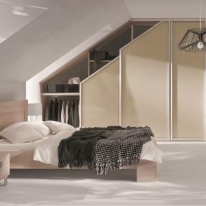 Garderobę można urządzić także w sypialni pod skosem dachowym wnękę zamykając drzwiami przesuwanymi wykonanymi na indywidualne zamówienie. Na zdj. system firmy Komandor. For. Komandor