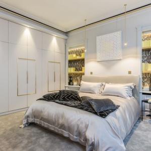 Przytulność w drugiej sypialni buduje miękki, aksamitny dywan w szarym kolorze oraz fronty zabudowy meblowej wykończone... skórą. Projekt: Gerard Faivre Paris.