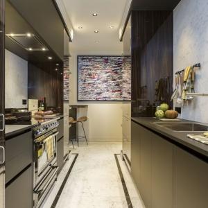 Podłogę w kuchni wykończono prawdziwym marmurem, idealnie harmonizującym z wykonaną na zamówienie zabudową kuchenną w przytulnych kolorach drewna mahoniowego. Projekt: Gerard Faivre Paris.