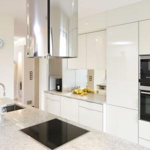Nowoczesna biała kuchnia jest nie tylko elegancka, ale i bardzo funkcjonalna. Sprzęty AGD umieszczono w wysokiej zabudowie, na wysokości umożliwiającej komfortowe z nich korzystanie. Projekt: Kinga Śliwa. Fot. Bartosz Jarosz