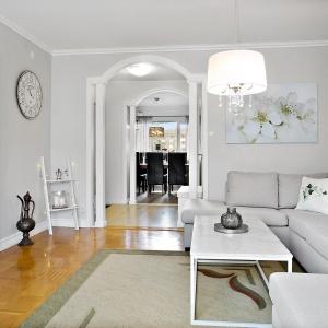 Romantyczny klimat w mieszkaniu budują lekkie, kobiece dodatki: stary tarczowy zegar, dekoracyjny żyrandol oraz obraz z kwiecistym motywem. Zdjęcia: Svenksfast.se