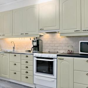Kuchnię urządzono w kremowym kolorze oraz klasycznej manierze. Frezowane fronty i dekoracyjne uchwyty nadają jej przytulny klimat. Zdjęcia: Svenksfast.se
