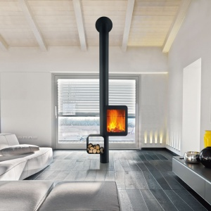 Nagrodzony Red Dot Design Award 2014 kominek Grappus to wyjątkowa instalacja, która wysubtelnia ogień i komponuje przestrzeń. Palenisko zostało wyniesione na odpowiednią wysokość, a po drugiej stronie, tuż nad podłogą jest miejsce na zapas drewna. Fot. Focus/Koperfam, kominek Grappus.