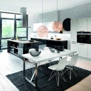 Propozycja zabudowy kuchennej do kuchni otwartej na salon i jadalnię. Wyspa z frontami w kolorze Cristall Schwarz. Fot. Häcker