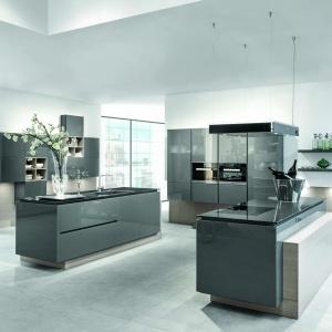 Kuchnia AV5090-GL Glass Lavagrau z szarymi, szklanymi frontami. Zabudowa kuchenna z dwiema wyspami, w których ulokowane zostały strefy gotowania i oddzielnie - zmywania. Fot. Häcker