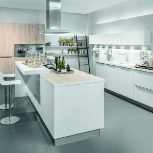 Nowoczesna kuchnia z obszerną wyspą AV2030 Polarweis. Chłód białych, błyszczących frontów ociepla dodatek drewna w zabudowie wysokiej. Fot. Häcker