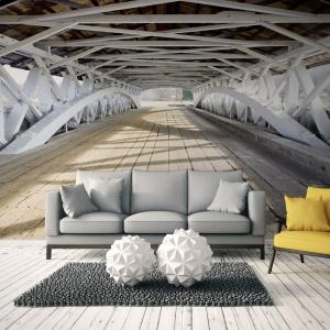 Widok daleko idącego drewnianego mostu wspaniale powiększa przestrzeń salonu. Wrażenie jest potęgowane przez idealnie dobraną kolorystykę desek na zdjęciu i podłogi w salonie, które zdają się niemal tworzyć jedną całość. Fot. Dekowizja.pl
