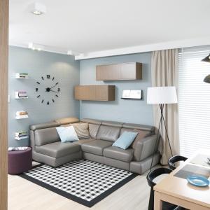 W tym salonie króują geometryczne motywy: kwadratowa mozaika na dywanie, asymetrycznie rozmieszczone szafki wiszące na ścianie czy w końcu okrągły zegar pozbawiony tarczy. Projekt: Joanna Morkowska-Saj. Fot Bartosz Jarosz