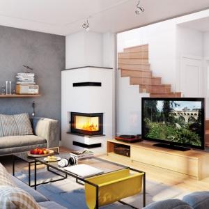 Narożnie przeszklony kominek, widoczny z różnych części domu, który został zastosowany do aranżacji salonu Domu w janowcach, stanowi atrakcyjny element dekoracyjny, buduje nastrój wnętrza i organizuje przestrzeń wokół. Fot. archonhome.pl