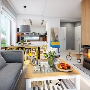Wnętrze Domu w rododendronach 11 N nawiązujące do atmosfery chłodnej klimatycznie, za to gościnnej i domowej atmosfery Północy. Detalem charakterystycznym dla architektury skandynawskiej jest naturalne drewno, które w naszej aranżacji króluje w obudowie kominka Blanka 8 kW. Fot. archonhome.pl