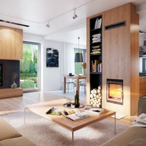 W salonie Domu w cytryńcach uwagę zwraca drewniana zabudowa kominka połączonego z regałem. Drewno i widok ognia w kominku z ułożonymi obok polanami to gwarancja, że czas spędzony w takim otoczeniu będzie czasem relaksu i odpoczynku. Fot. archonhome.pl