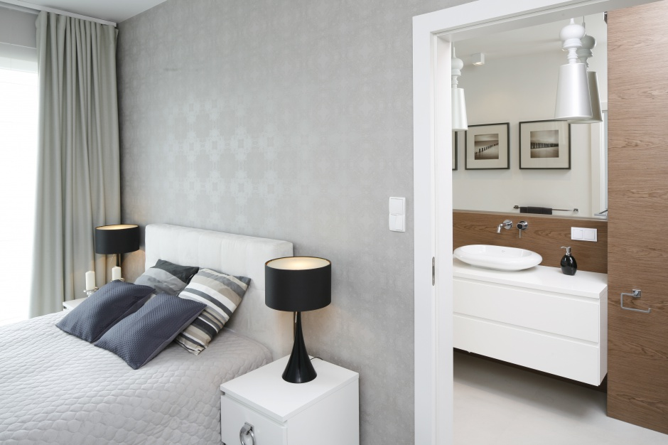 W nowoczesnej, kobiecej sypialni rządzą jasne, połyskujące szarości. Ciemne dodatki dekoracyjne stanowią efektowny kontrast. Projekt: Małgorzata Galewska. Fot. Bartosz Jarosz